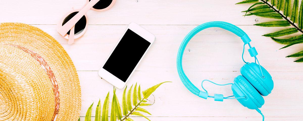 Smartphone, auriculares azul turquesa y gafas de sol sobre fondo de madera blanca y hojas de palmera